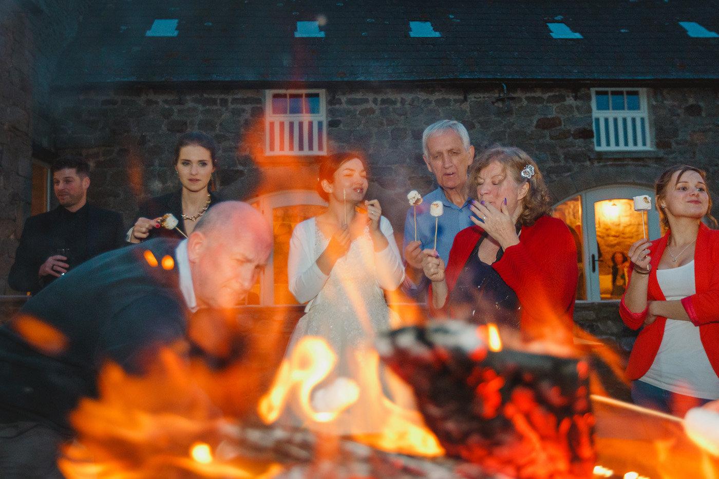 wedding guests around campfire eating smores northside farm
