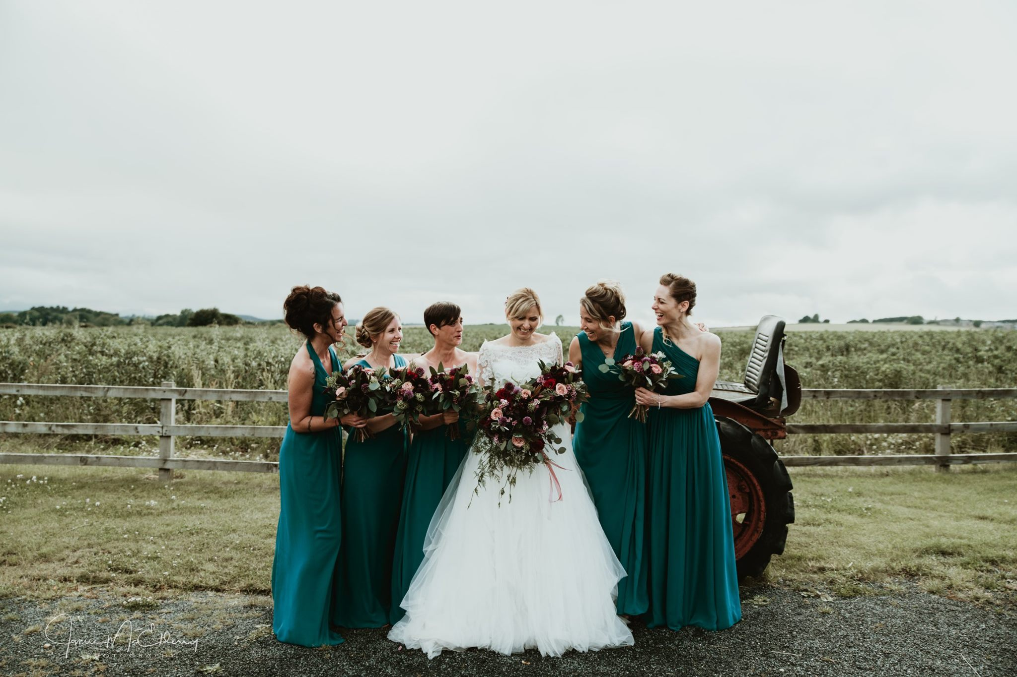 bride and bridesmaids posing next to tractor fram wedding