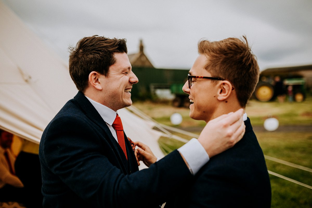 groom and best man laughing beside teepees