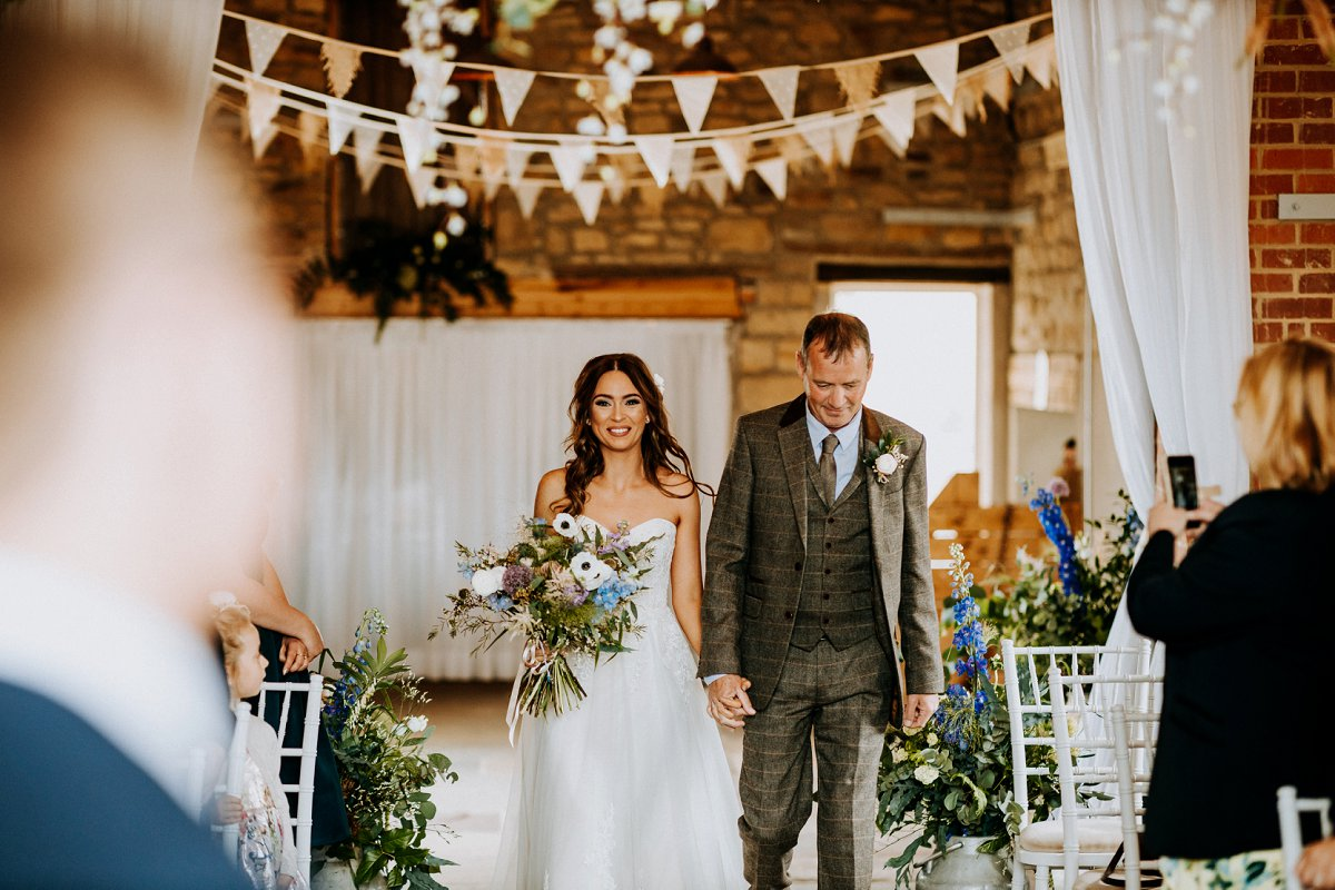bride and groom holding hands barn wedding with bunting