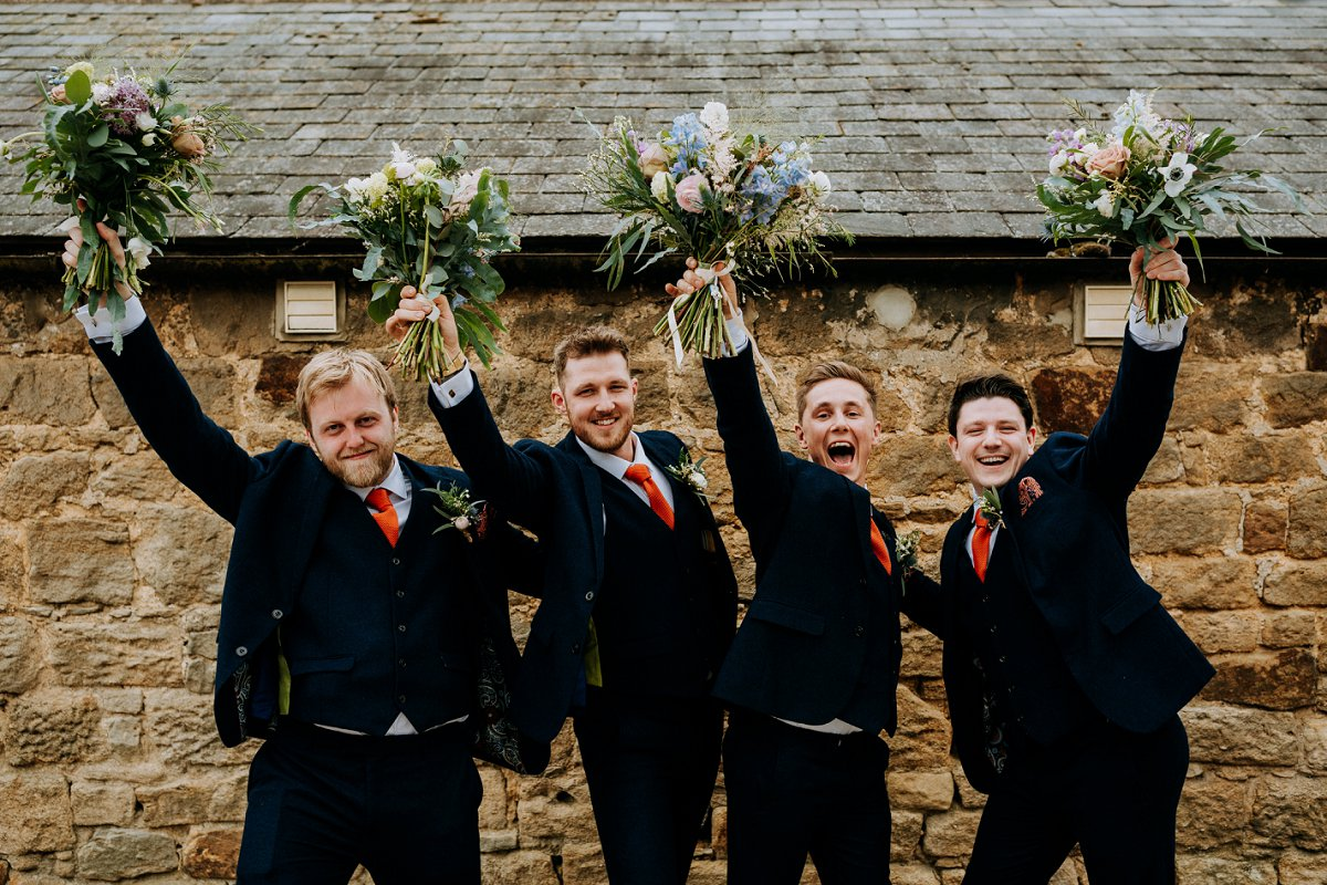 groomsmen with bouquets in navy suits with orange ties