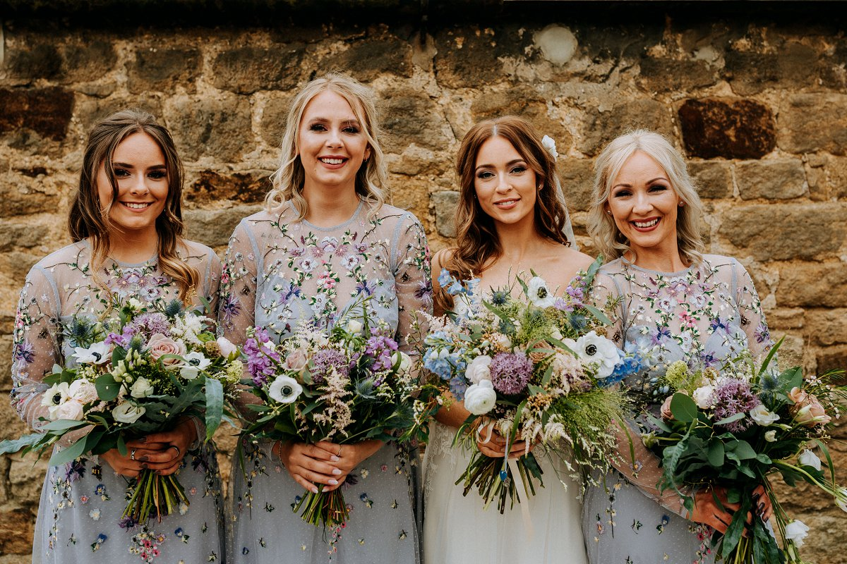 bride and bridesmaids in pale blue floral dresses with blue and ivory bouquets
