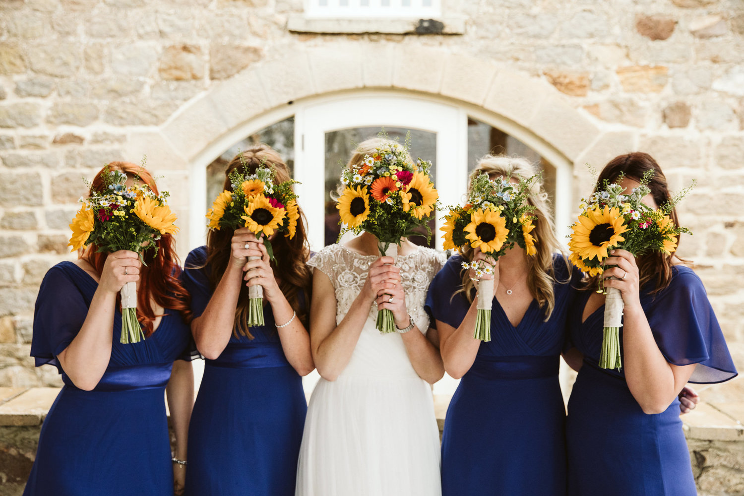 bride and bridesmaids hiding faces with sunflower bouquets