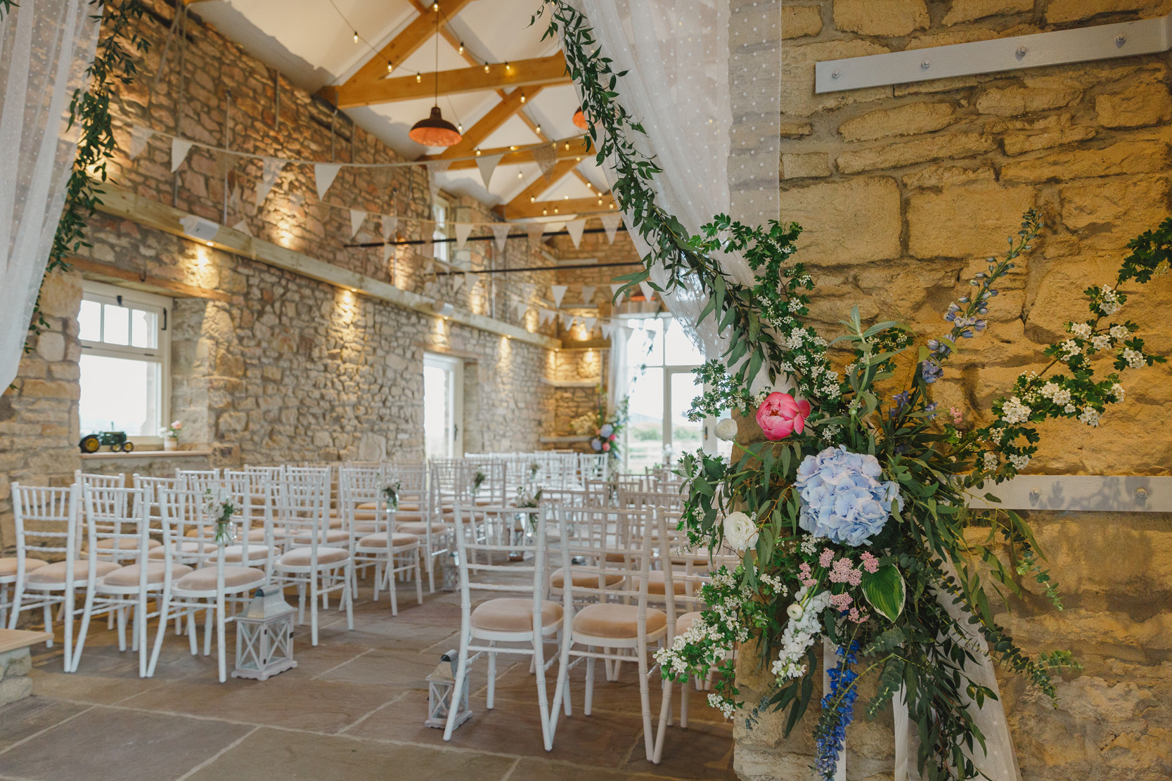 barn wedding ceremony decorated with flowers and foliage