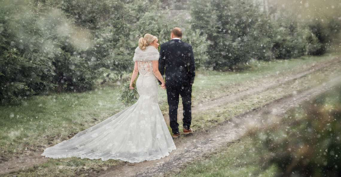 bride and groom walking hand-in-hand winter wedding in northumberland