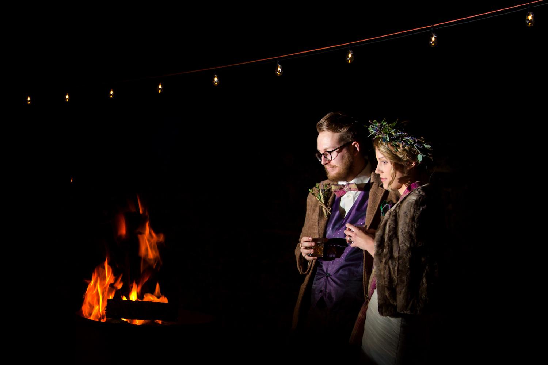 bride and groom beside open fire winter wedding in northumberland